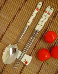 Palillos chinos de metal junto a una cuchara.