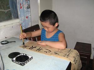 Un niño está practicando la caligrafía.