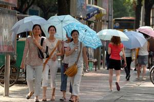Chicas chinas llevando un paraguas para protejerse del sol.