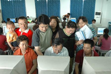 Unos adultos chinos están estudiando el manejo del ordenador.